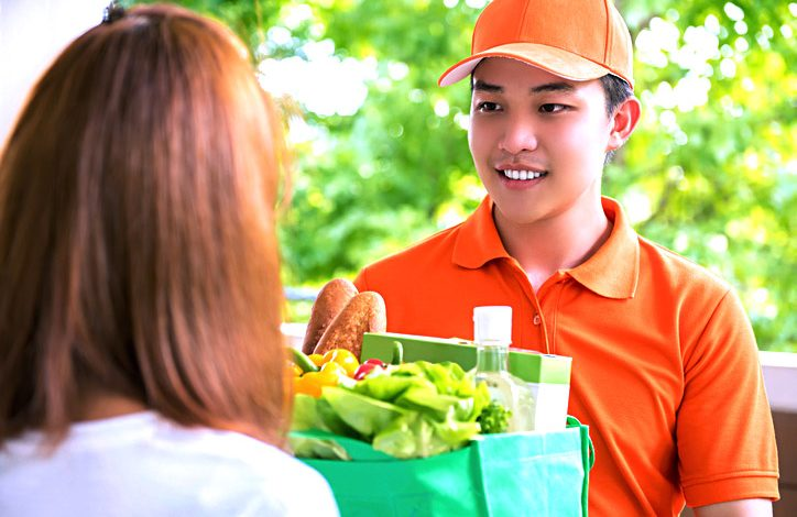 Delivery man delivering food to a woman at home